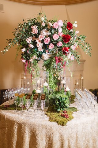 champagne-glass-escort-cards-floral-table-pink-red-flowers-moss-candles-patterned-linen