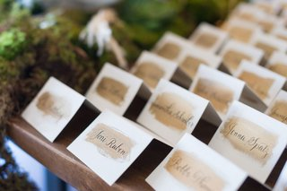 tent-escort-cards-on-wood-table-black-calligraphy-gold-brush-stroke-paint-detail
