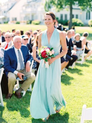 bridesmaid-walking-down-grass-aisle-in-mint-green-blue-v-neck-bridesmaid-dress-pink-peony-bouquet