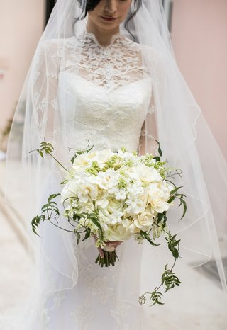 bride-holding-ivory-bouquet-composed-of-roses-gardenias-stephanotis-blossoms-green-vines