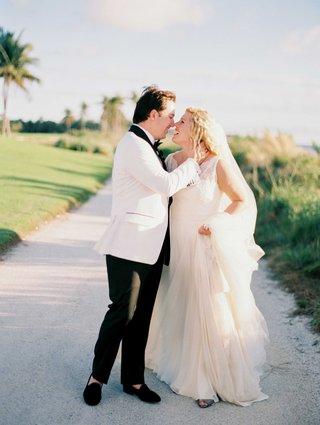 groom-in-black-tuxedo-pants-white-tuxedo-jacket-with-black-lapels-and-navy-velvet-slippers-bride