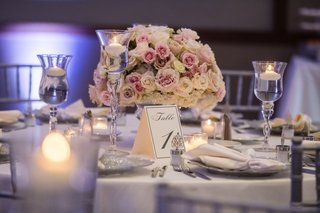 wedding reception round table silver chairs and table number floating candles white pink roses