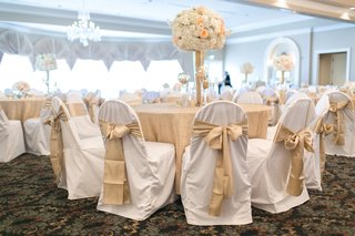 wedding-reception-with-tables-covered-in-gilt-tablecloths-chairs-in-vanilla-seat-covers-gold-bows