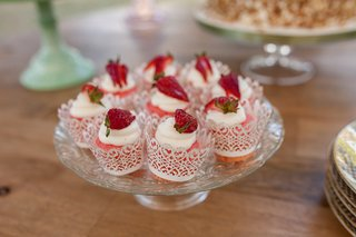 strawberry-and-cream-treats-in-vintage-inspired-cups-on-glass-cake-tray-wood-table-dessert-table