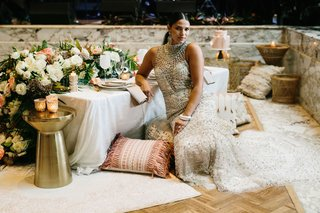 model-bride-styled-shoot-high-neck-beaded-wedding-dress-gold-stool-ottoman-floor-pillow-morocco