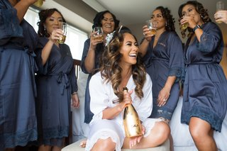 wedding photo getting ready bride in white robe bridesmaids in navy sipping champagne gold bottle