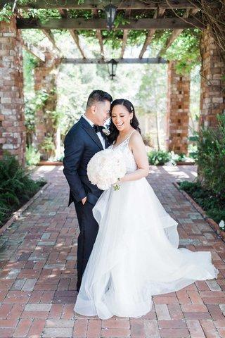 wedding-portrait-brick-flooring-and-wood-beams-greenery-black-tuxedo-and-hayley-paige-wedding-dress