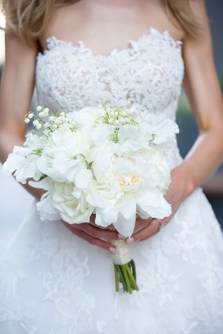 bride-with-blonde-hair-strapless-reem-acra-wedding-dress-holding-white-bouquet-manicure