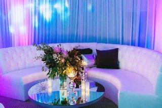 wedding-reception-white-lounge-furniture-mirror-coffee-table-flower-arrangement-bright-lighting