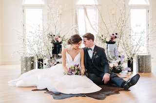 styled-shoot-wedding-inspiration-bride-in-hayley-paige-groom-in-suit-sitting-on-cow-skin-rug
