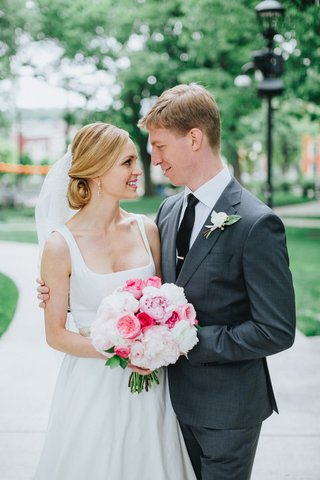 blonde-bride-with-low-chignon-bun-groom-in-grey-suit-with-arm-around-bride-peony-bouquet