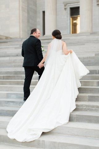bride-in-justin-alexander-plain-ball-gown-holds-train-walks-up-steps-with-groom