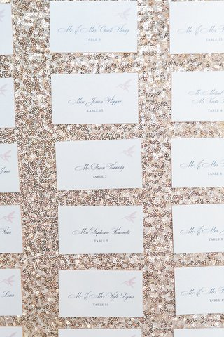 white-wedding-reception-escort-cards-with-pink-hummingbird-against-a-gold-sequined-backdrop