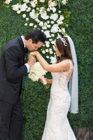 groom-in-calvin-klein-kisses-hand-of-bride-in