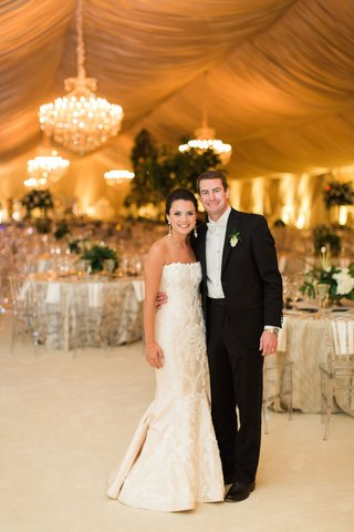 bride-in-strapless-romona-keveza-wedding-dress-groom-in-suit-with-white-bow-tie-drapery-chandeliers