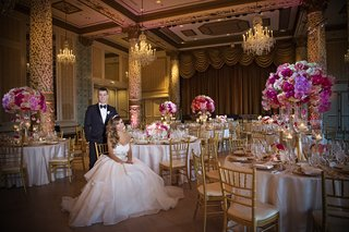bride-in-alyne-ball-gown-with-large-belt-sits-in-chair-in-front-of-groom-in-tuxedo-in-drake-hotel