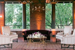 wedding-reception-brick-walls-chandeliers-gold-coffee-table-velvet-sofa-settee-armchairs-lounging