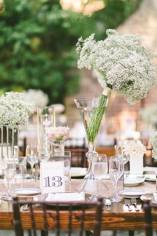ranch-wedding-reception-with-wood-table-white-flowers-and-table-number-with-a-golden-glitter-edge
