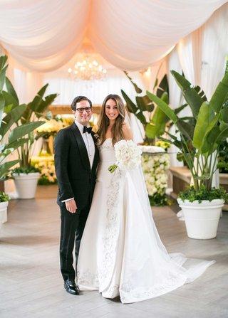bride-in-oscar-de-la-renta-wedding-dress-with-white-peony-bouquet-groom-in-tuxedo-bow-tie-by-drapery