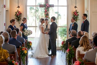 bride-in-romona-keveza-wedding-dress-at-altar-with-groom-officiant-and-wedding-party-cross-pews