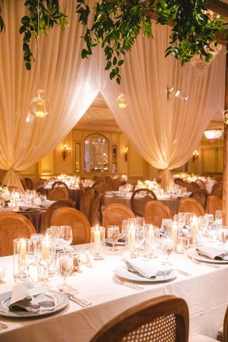 wedding-reception-greenery-glass-orb-candles-overhead-long-table-wood-cane-chairs-candles-low-flower