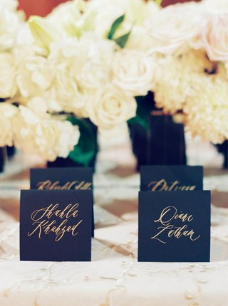 wedding-reception-escort-cards-black-stationery-card-stock-with-gold-calligraphy-white-rose-flowers