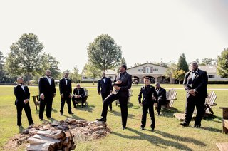 groom-and-groomsmen-in-suits-tuxedos-on-lawn-of-private-estate-farm-with-wood-lounge-chairs-unique