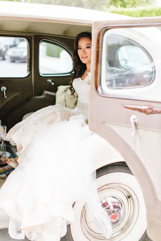 bride-in-trumpet-wedding-dress-getting-into-or-out-of-a-vintage-packard-car-at-ceremony