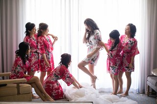 bride-in-white-floral-robe-stepping-into-wedding-gown-while-bridesmaids-in-pink-robes-help