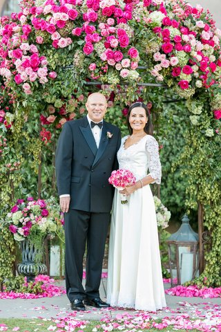 vow-renewal-husband-and-wife-under-pink-rose-pergola-with-wedding-dress-pink-bouquet-tuxedo