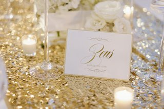wedding-reception-table-with-gold-sequined-runner-votive-candles-white-roses-and-zeus-table-name