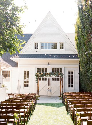 wedding-ceremony-outside-string-lights-wood-branch-chuppah-greenery-renovated-victorian-farmhouse
