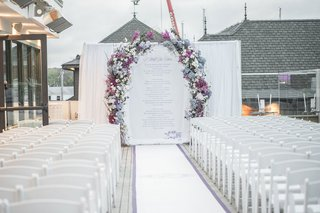 outdoor-wedding-with-ceremony-arch-featuring-blue-and-purple-flowers-white-chairs