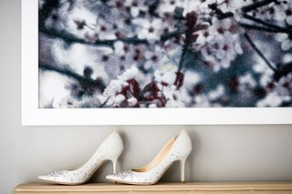 white-pumps-with-rhinestones-crystals-jimmy-choo-on-shelf-with-artwork-on-wall