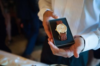 bride-gifts-her-groom-a-beautiful-watch-with-brown-leather-band-and-gold-face-in-blue-box