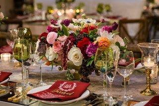 low-wedding-centerpiece-green-glassware-white-red-pink-orange-flowers-monogram-menu-burgundy-napkin