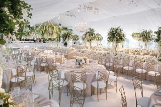 white-tented-wedding-reception-flower-chandelier-gold-chairs-high-low-centerpieces-tree-centerpiece