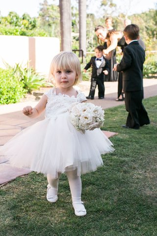flower-girl-in-white-dress-tulle-skirt-with-white-tights-leggings-and-shoes-bouquet-blonde-hair