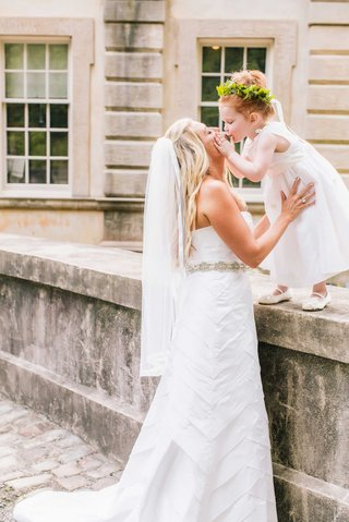bride-in-anne-barge-wedding-dress-kissing-red-head-flower-girl-in-white-dress-greenery-floral-crown