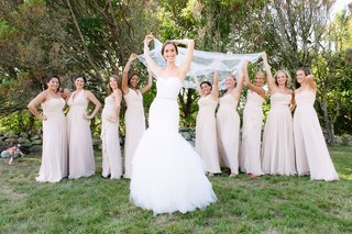 bridesmaids-in-mismatched-long-bridesmaid-dresses-holding-veil-bride-in-pnina-tornai-for-kleinfeld