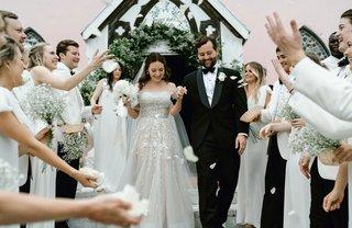 wedding-ceremony-exit-pink-chapel-harbour-island-bahamas-white-flower-petal-toss-guests-bridesmaids