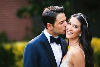 groom-in-navy-blue-tuxedo-with-black-bow-tie-side-part-kissing-bride-on-cheek-smiling
