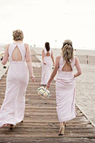 bridesmaids-with-light-pink-bridesmaid-dresses-keyhole-back-walking-on-wood-plank-boardwalk-sand