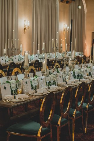 wedding-reception-long-table-with-gold-green-chairs-tall-taper-candles-white-greenery-flowers-luxury