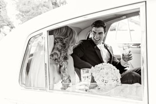 black-and-white-photo-of-bride-and-groom-with-champagne-in-getaway-car-from-ceremony-to-reception