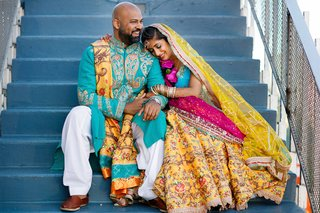pakistani-couple-in-traditional-mehndi-attire-of-yellow-blue-pink-and-white-with-beads-and-jewels