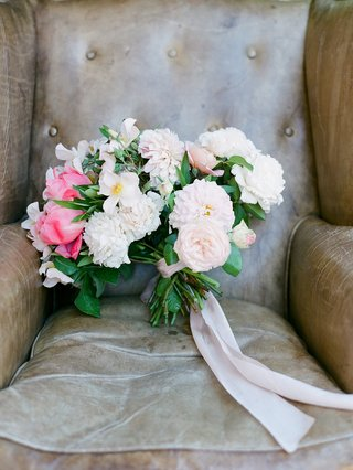 green-stems-tied-with-pink-ribbon-pink-peony-ranunculus-garden-rose-and-bay-leaf-leather-chair