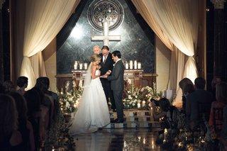 bride-and-groom-at-church-decor-ceremony-look-cross-candles-low-flower-arrangement-oscar-de-la-renta