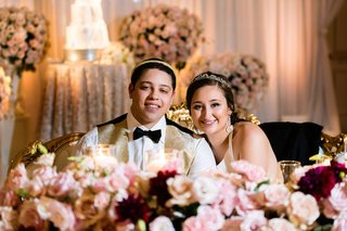 wedding reception bride and groom in gold vest with headbands at sweetheart table pink rose burgundy marsala flowers