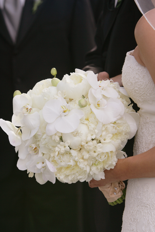 bride-holding-white-flower-bouquet-with-orchid-peony-and-stephanotis-blooms